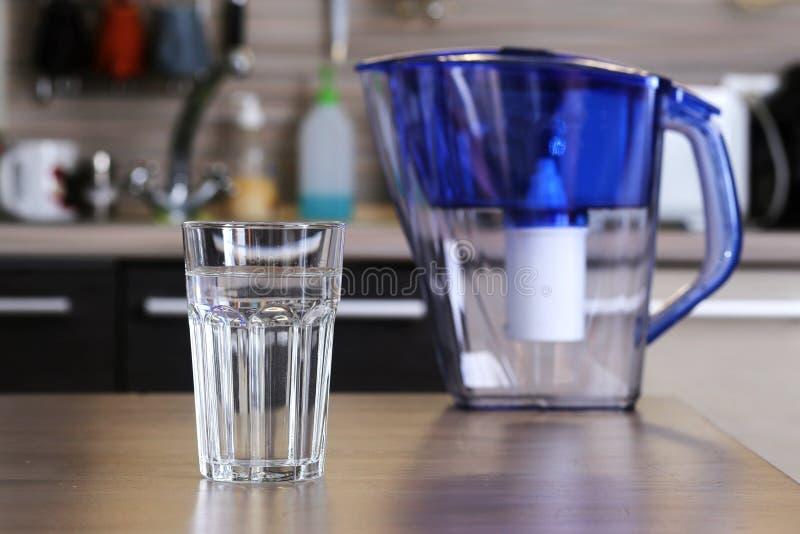 Glas van schone water en filter voor het schoonmaken van drinkwater op de lijst in de keuken Reiniging van drinkwater thuis stock afbeelding