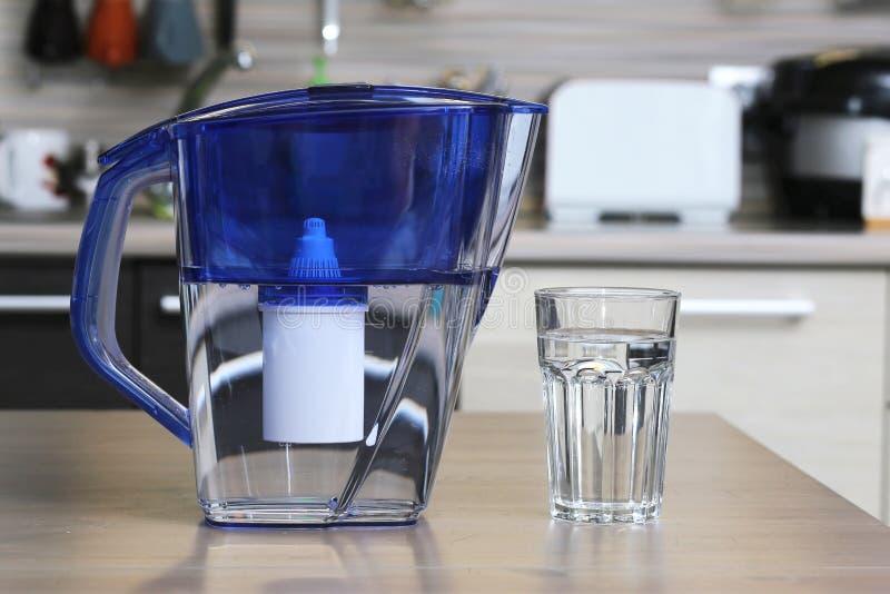 Glas van schone water en filter voor het schoonmaken van drinkwater op de lijst in de keuken Reiniging van drinkwater thuis royalty-vrije stock fotografie