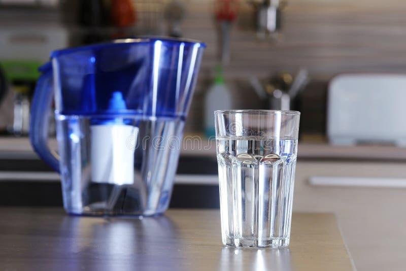 Glas van schone water en filter voor het schoonmaken van drinkwater op de lijst in de keuken Reiniging van drinkwater thuis stock foto