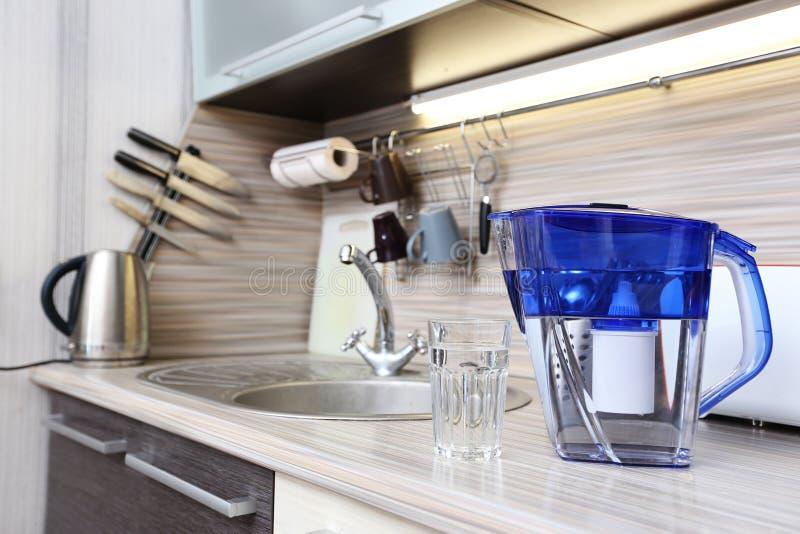 Glas van schone water en filter voor het schoonmaken van drinkwater op de lijst in de keuken Reiniging van drinkwater thuis royalty-vrije stock foto's