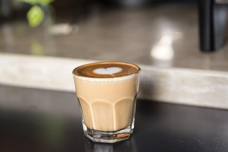 Glas van smakelijke latte met liefdekunst op concrete geweven achtergrond stock foto's