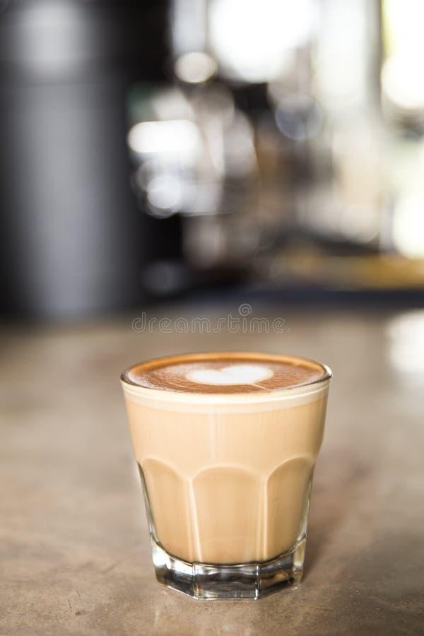 Glas van smakelijke latte met liefdekunst op concrete geweven achtergrond stock afbeelding