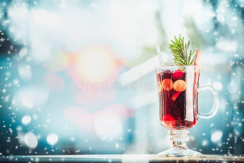 Glas van traditionele overwogen wijn of stempel op lijst bij de ijzige achtergrond van de de winterdag met sneeuw stock afbeelding