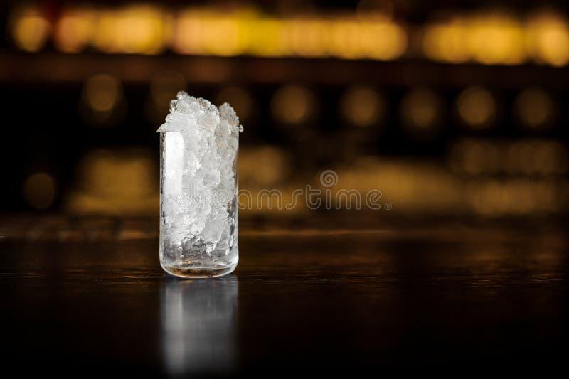 Glas van verpletterd ijs die zich op de bartribune bevinden stock fotografie