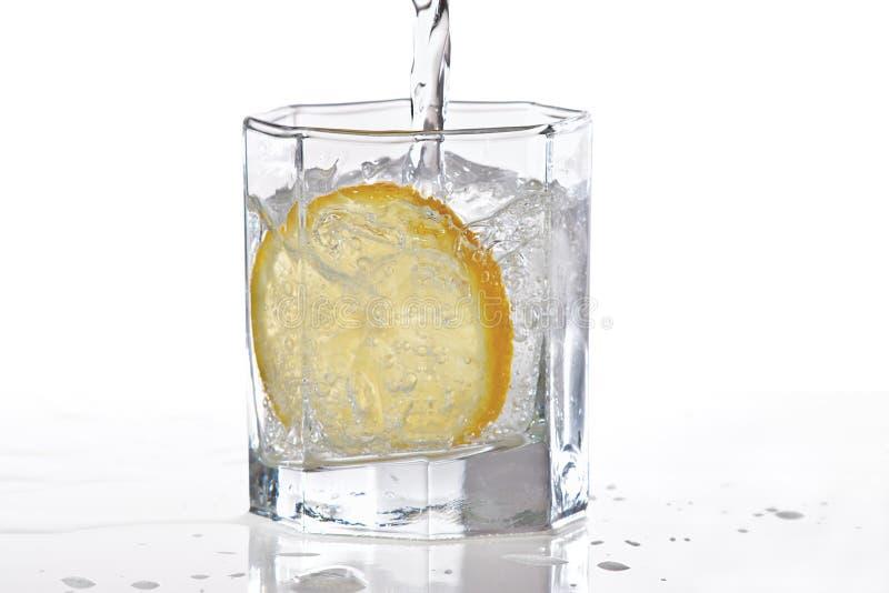 Glas van water, ijs en plak van citroen met plons royalty-vrije stock afbeelding