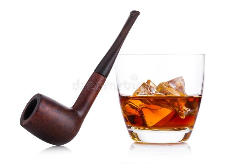 Glas van whisky met ijsblokjes en uitstekende rokende pijp op whit royalty-vrije stock afbeelding