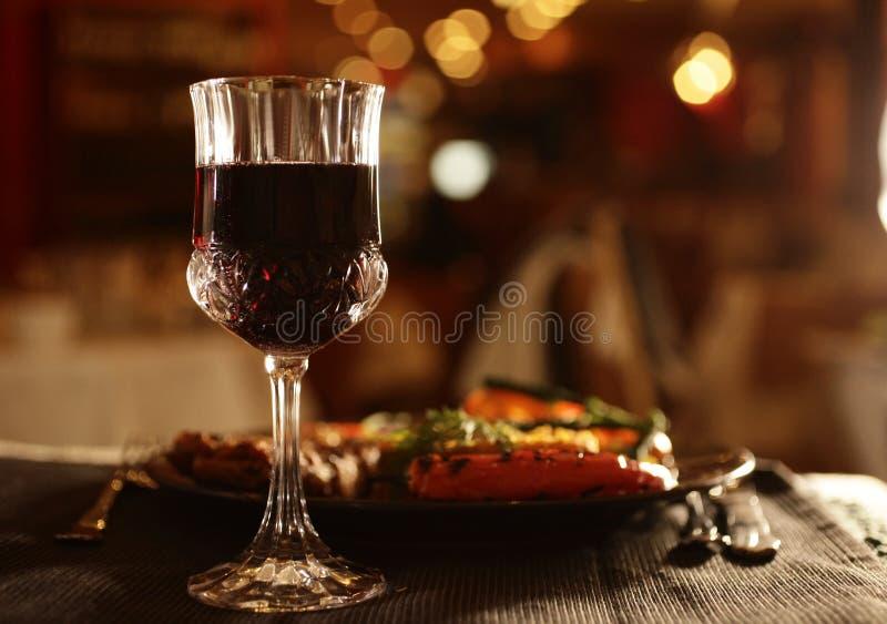 Glas van wijn en diner naast stock foto