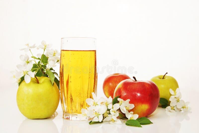 Glas vers appelsap en rijpe appelen stock afbeeldingen