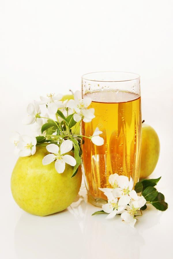 Glas vers appelsap en rijpe groene appelen stock afbeeldingen