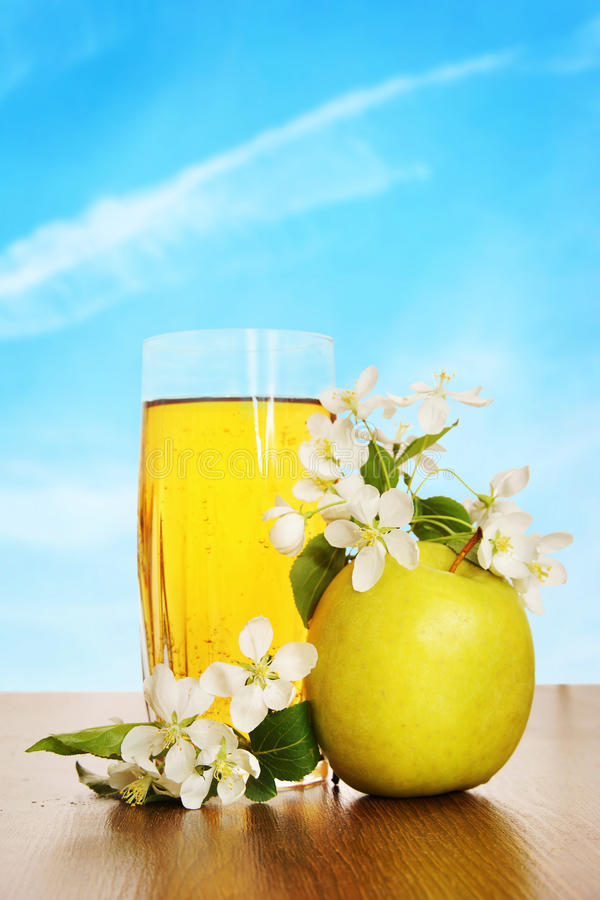 Glas vers appelsap op houten oppervlakte tegen blauwe hemel stock afbeelding