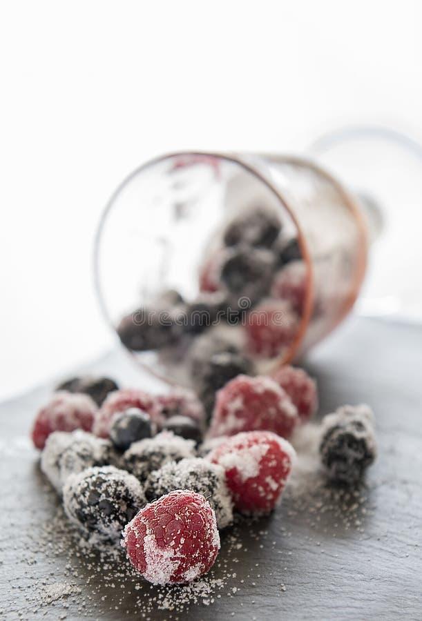 Glas verschüttete Beeren und Zucker auf einer Schieferplatte stockfotografie