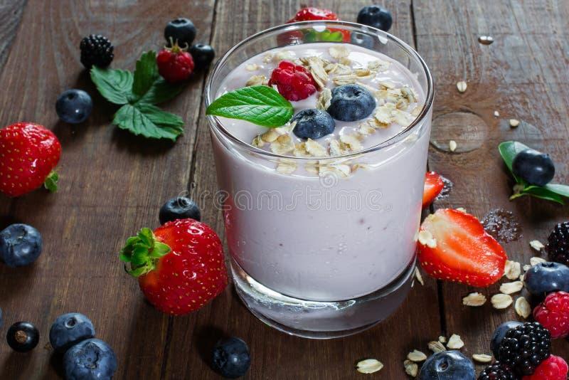 Glas verse gemengde bessen, granola en yoghurt in een glas en royalty-vrije stock afbeelding