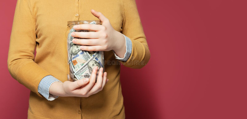Glas voll Geld in den Händen H?nde, die Stapel der M?nzen sch?tzen lizenzfreie stockfotos