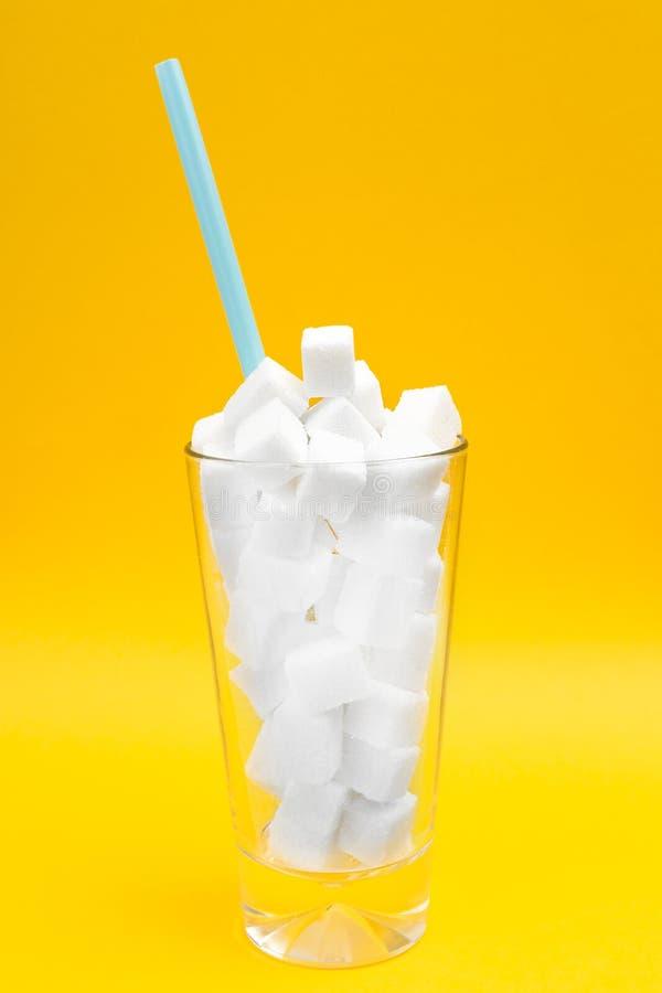 Glas voll von den Zuckerwürfeln über yellowbackground Ungesundes Di?t- und Diabeteskonzept Kopieren Sie Raum f?r Text lizenzfreie stockbilder