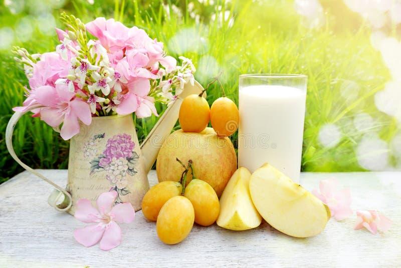 Glas von Milch, von Apfelfrucht und von rosa Blume auf weißer hölzerner Tabelle mit Hintergrund des grünen Grases stockfoto