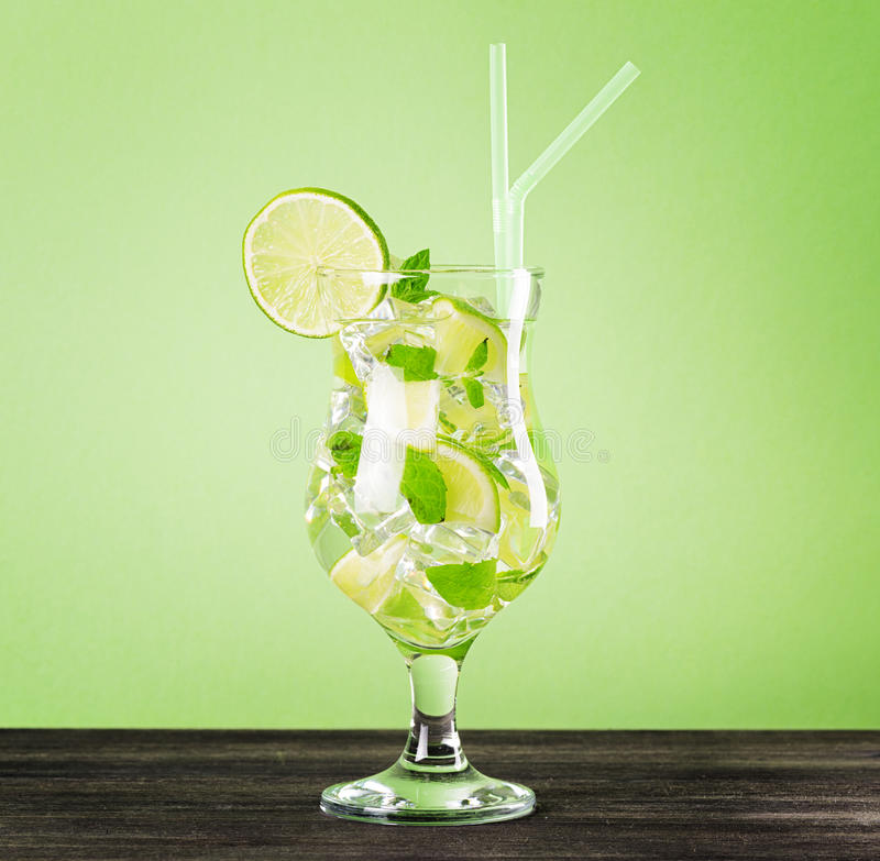 Glas von mojito Cocktail auf grünem Pastellhintergrund stockfotografie