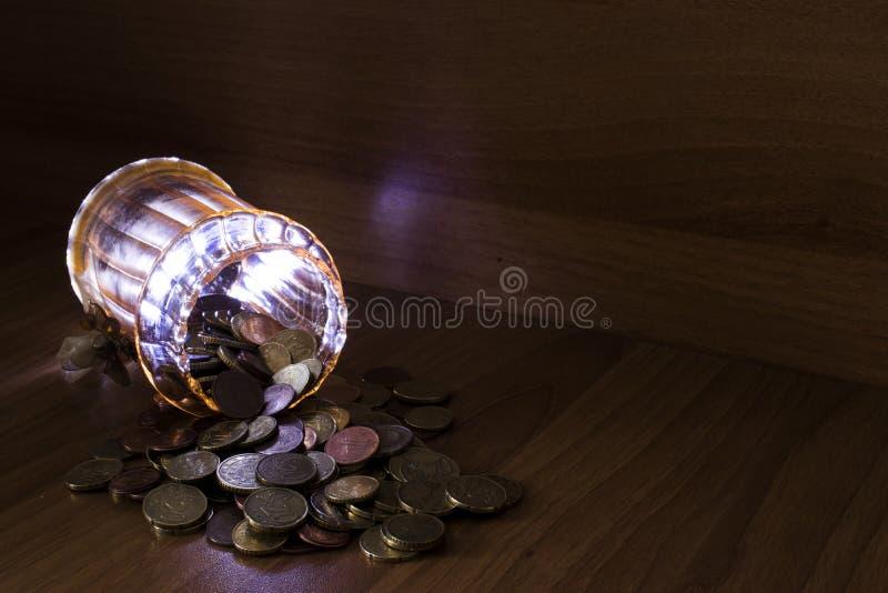 Glas von Glas voll von Euromünzen auf einer Tabelle unter Verwendung der hellen Malerei stockbilder