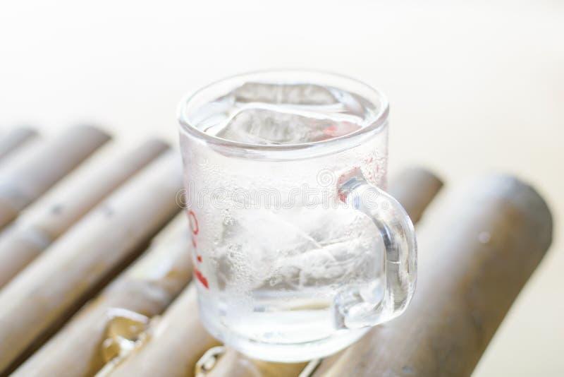 Glas Wasser auf einem Holztischhintergrund stockfotos