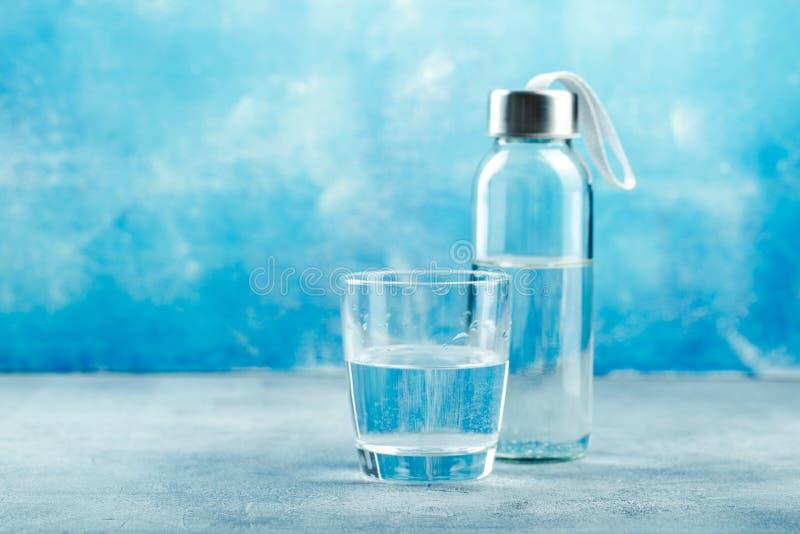 Glas Wasser mit einer Flasche stockfotografie