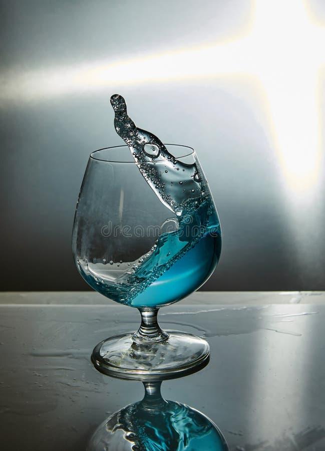 Glas Wasser mit einer Welle auf einem grauen Hintergrund lizenzfreies stockfoto