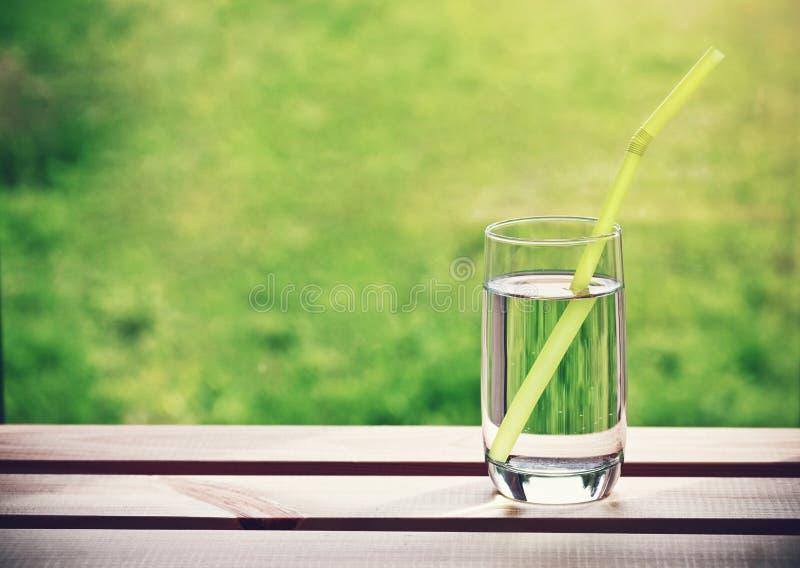 Glas Wasser mit Rohr stockfotografie