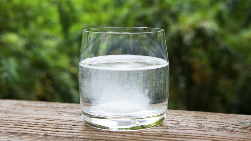 Glas Wasser mit schäumender Tablette lizenzfreie stockfotos