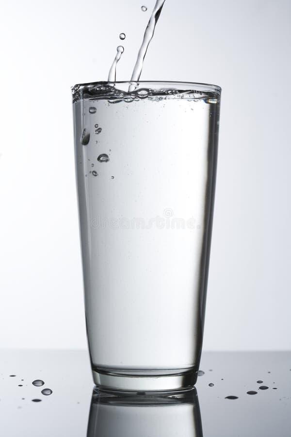 Glas Wasser mit Tropfenfänger stockfotos
