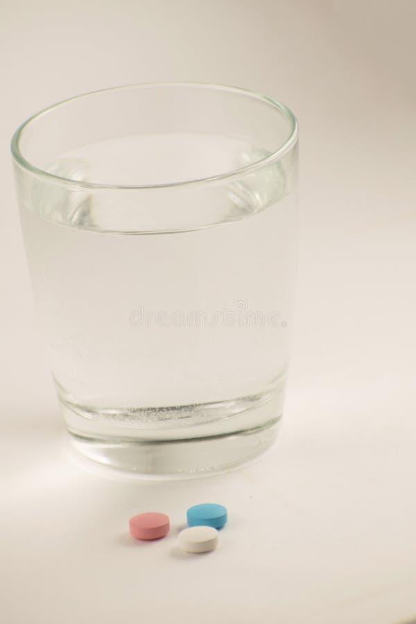 Glas Wasser und Pillen auf weißem Hintergrund Ein Glas Wasser und Vitamine Gesunder Lebensstil, Ernährungsergänzungen lizenzfreies stockfoto