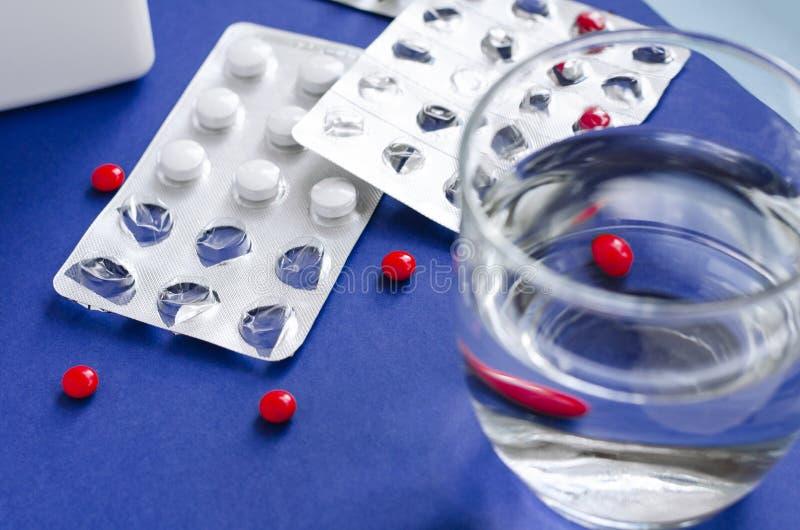 Glas Wasser und Pillen Nehmen der Pillen stockfotos