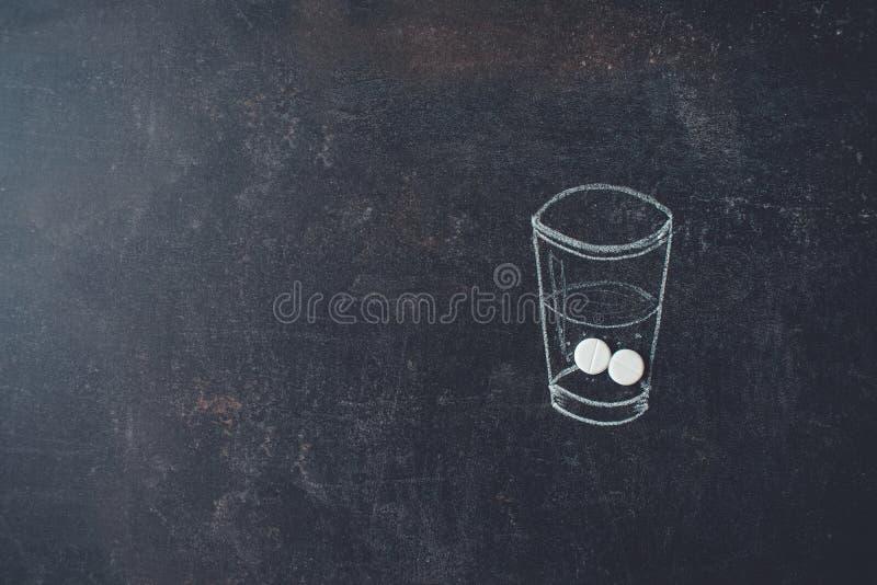 Glas Wasser und Pillen weissen gezeichnet auf Tafel Medizin, Gesundheitswesen und Leutekonzept lizenzfreies stockfoto