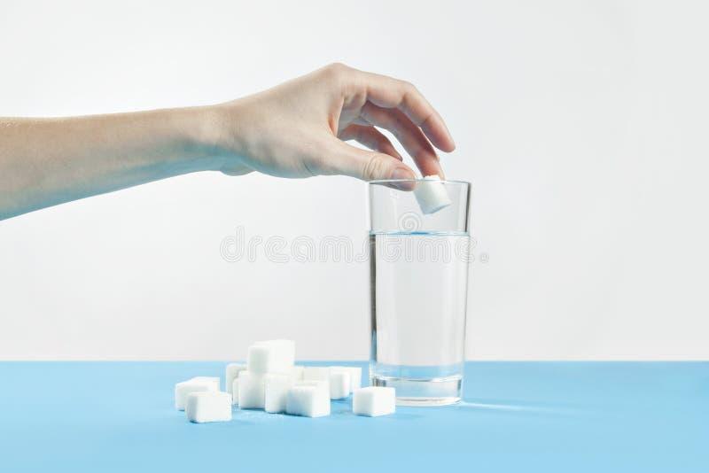 Glas Wasser- und Würfelzucker, Diabeteskrankheit, süße Sucht, Handtropfen ein Zucker lizenzfreie stockfotos
