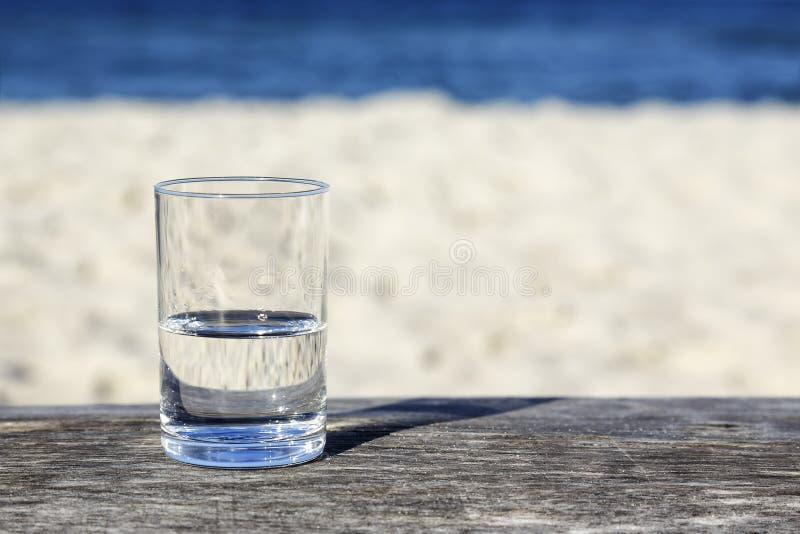 Glas water dat halfvol is stock foto's