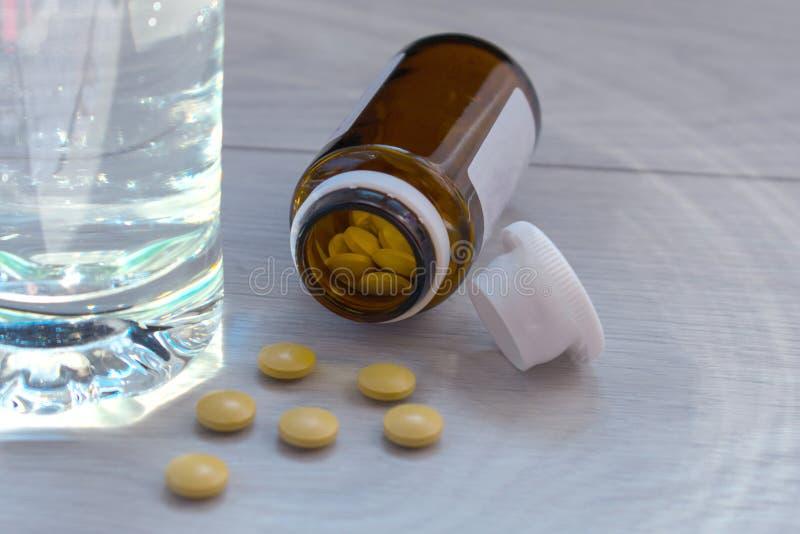Glas water en pillen op de lijst Boven ruimte of grafiek stock foto's