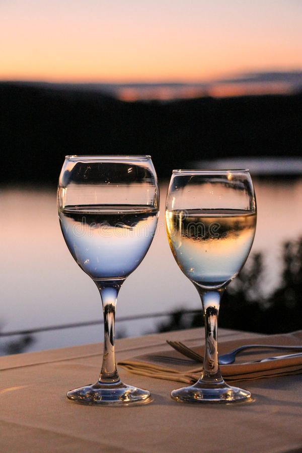 Glas water en glas wijn op een lijst in een restaurant met een zonsondergangmening bij de meermarathon, Griekenland stock afbeelding