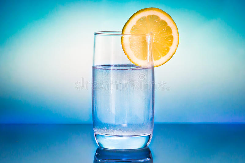 Glas of water with lemon. Glash of water with lemon on a blue blurred background royalty free stock photos