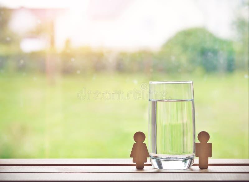 glas water met houten vrouw en de mens stock foto's