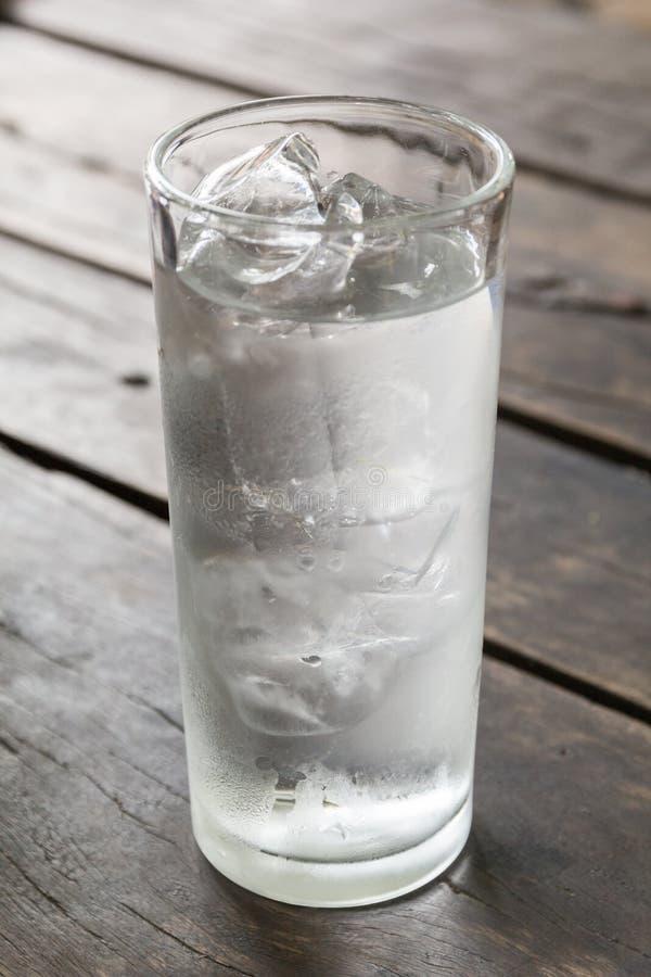 Glas water met ijs op de houten lijst stock afbeeldingen