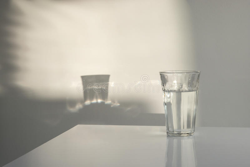 Glas of water with reflections stock photography