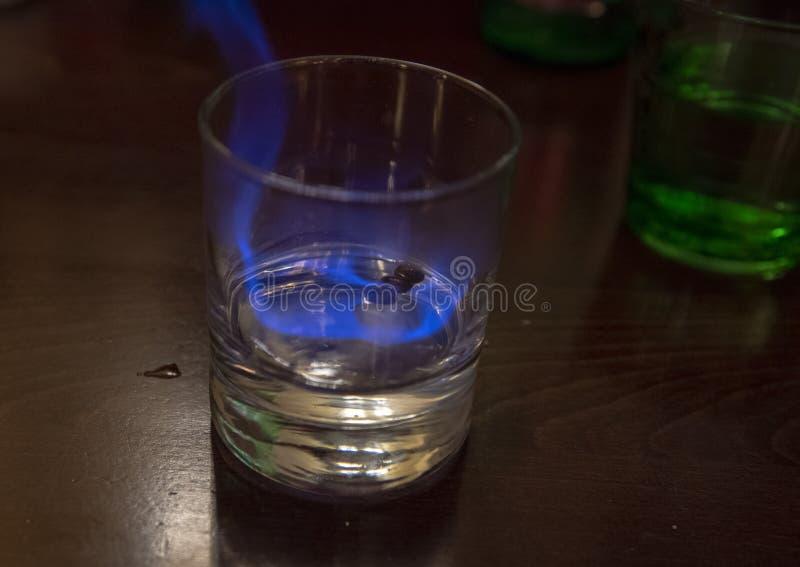 Glas weißes sambuca mit Kaffeebohnen, in Flammen lizenzfreie stockbilder