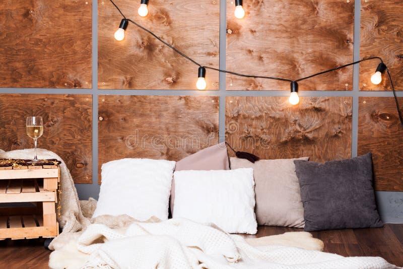 Glas Weißwein im modernen Dachbodeninnenraum mit heller Girlande auf hölzerner Wand stockfotografie