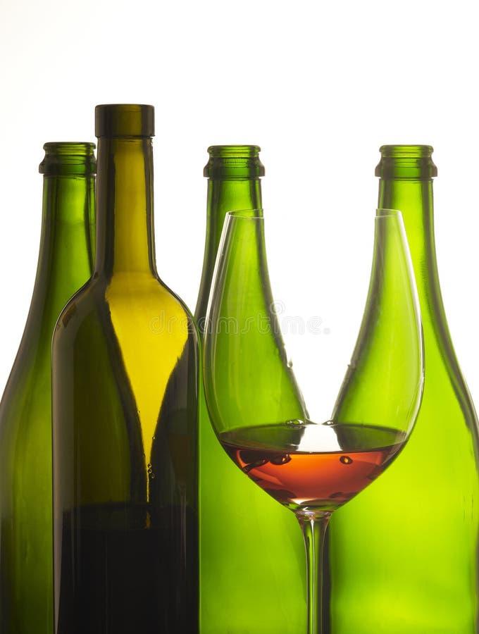 Glas Wein mit Flaschen lizenzfreie stockbilder