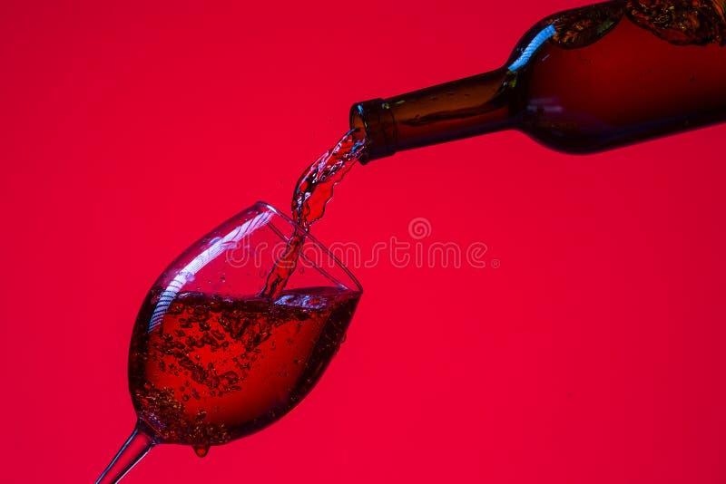 Glas Wein und Flasche mit ausgießendem Flüssigkeit Gegen Rot lizenzfreie stockfotografie