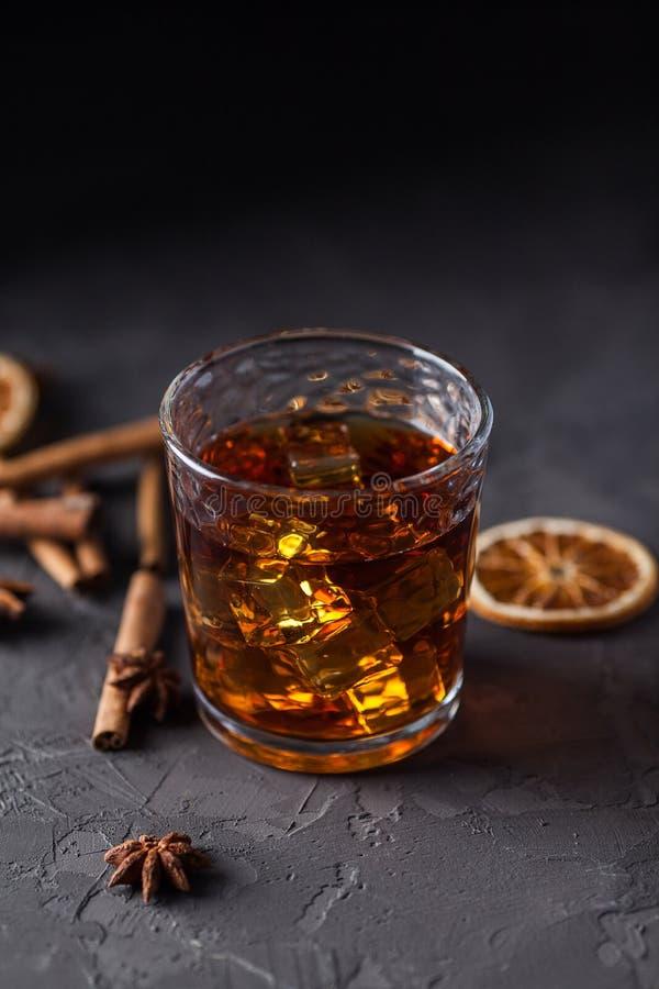 Glas Weinbrand oder Whisky, Gew?rze und Dekorationen auf dunklem Hintergrund Saisonfeiertagskonzept stockfoto