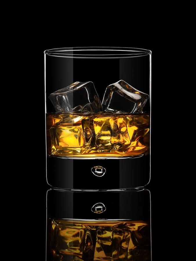 Glas Whisky auf einem schwarzen Hintergrund stockbilder