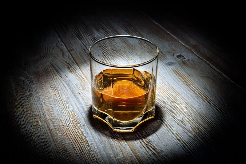 Glas Whisky auf einem Weinleseholztisch auf einem schwarzen Hintergrund lizenzfreie stockfotografie