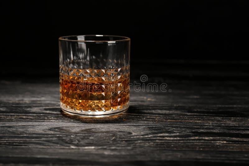 Glas Whisky auf Holztisch gegen schwarzen Hintergrund lizenzfreies stockbild