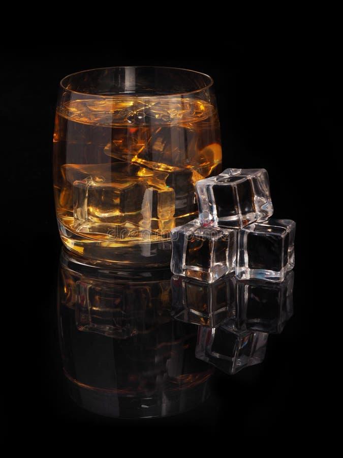 Glas whisky en ijs op een zwarte achtergrond royalty-vrije stock foto