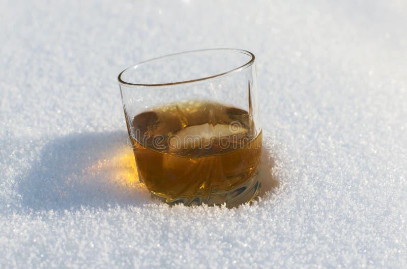 Glas Whisky im Schnee stockbild
