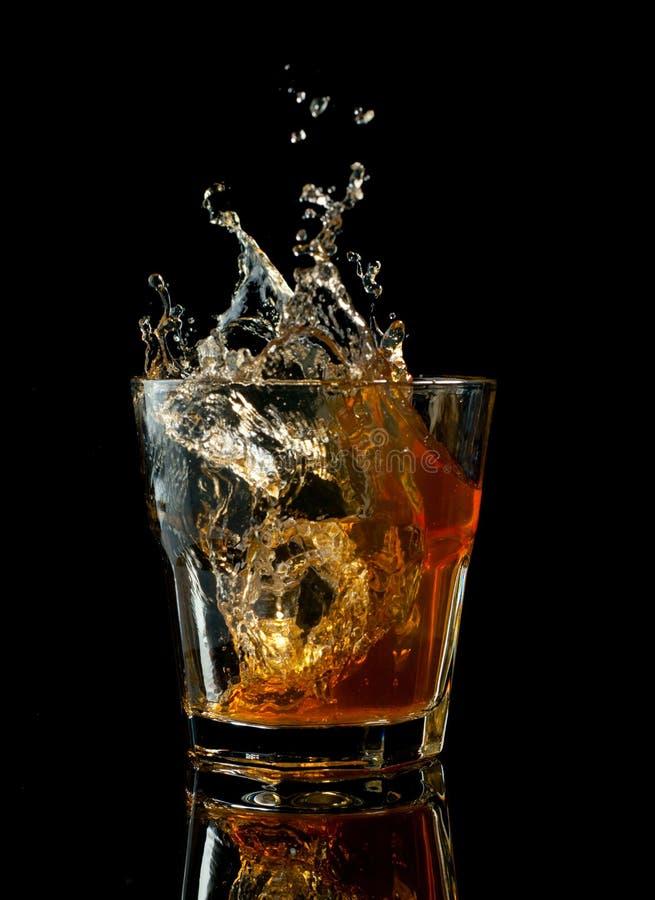 Glas whisky met plons, op zwarte wordt geïsoleerd die royalty-vrije stock afbeelding