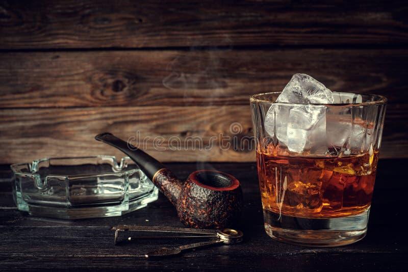 Glas Whisky mit Eis und Rohr auf einem hölzernen Hintergrund lizenzfreie stockfotografie